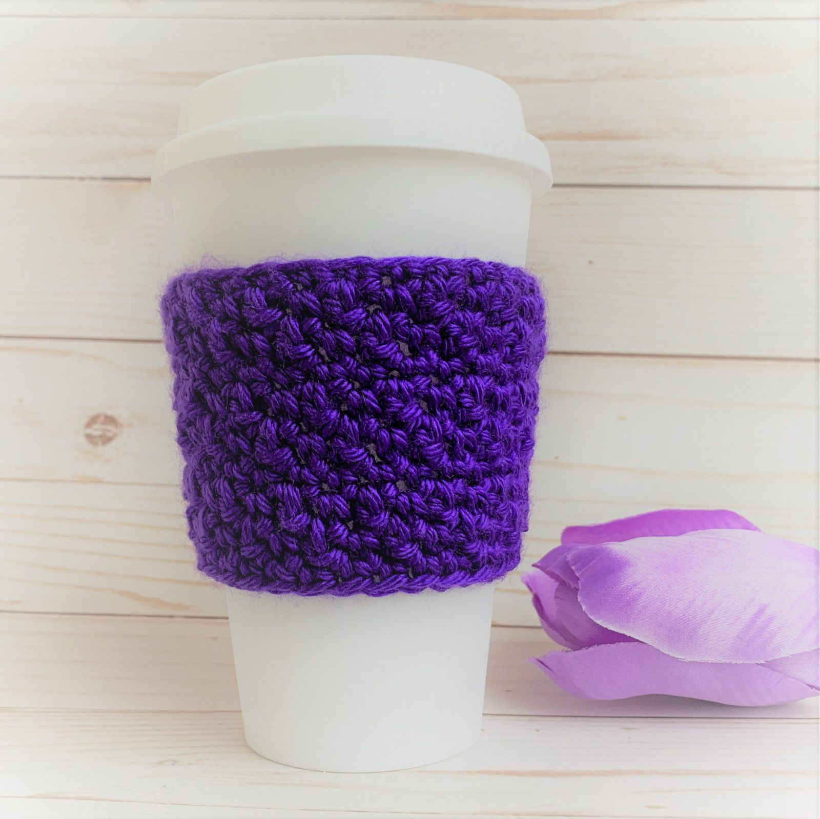 """Winter Hills Cozie"" in purple on a reusable travel mug. Purple tulip in background"