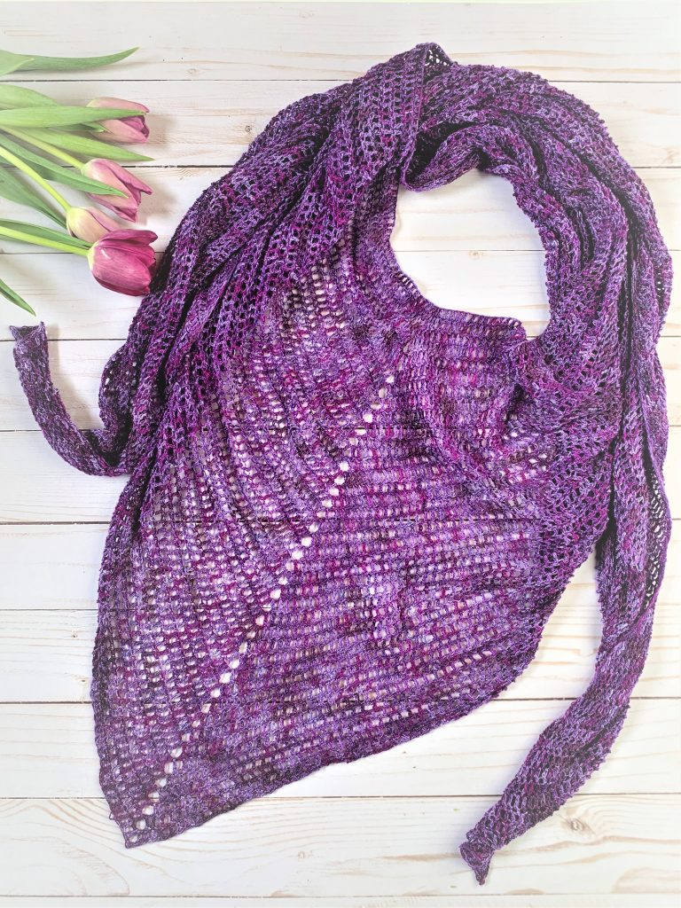 Amethyst Scarf laid flat with fresh purple tulips to the side, over a white wooden planked backing