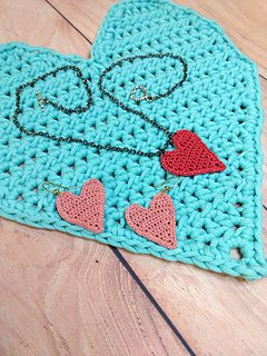 Heart shaped crocheted earrings and necklace placed on a crocheted heart shaped placemat.