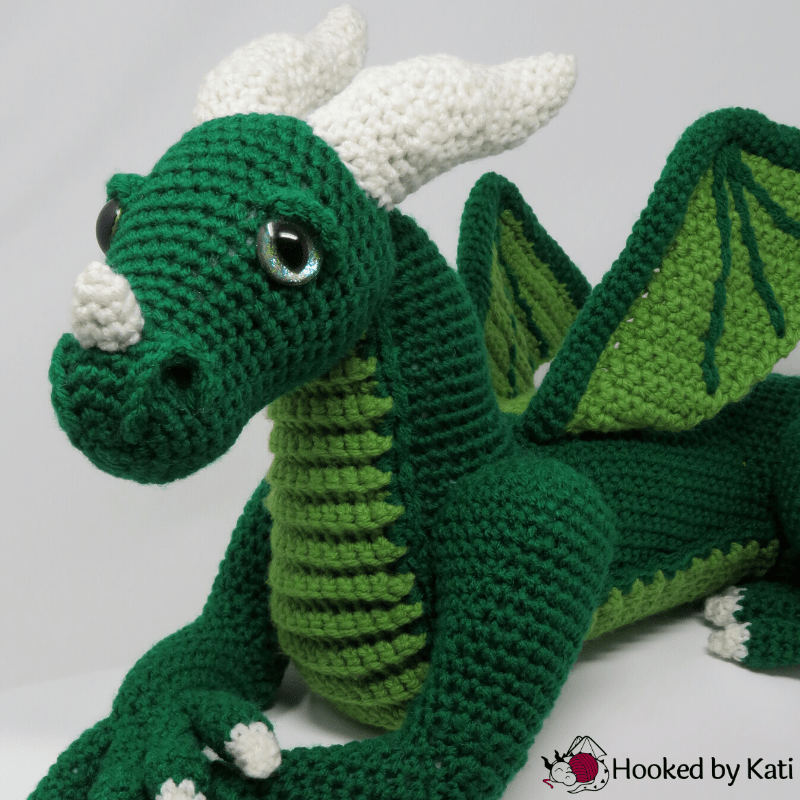 A green amigurumi dragon designed by HookedByKati.